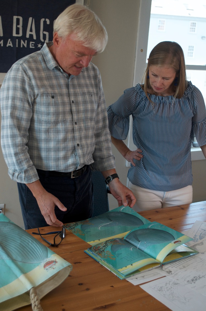 Chris Van Dusen and Sea Bags' Product Line Manager Tara Knupp look at the finished design on a recycled sail cloth tote