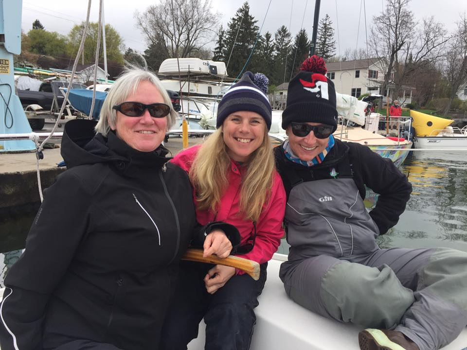 Members of the Sea Bags Women's Sailing Team wait for wind aboard their J/24 sailboat