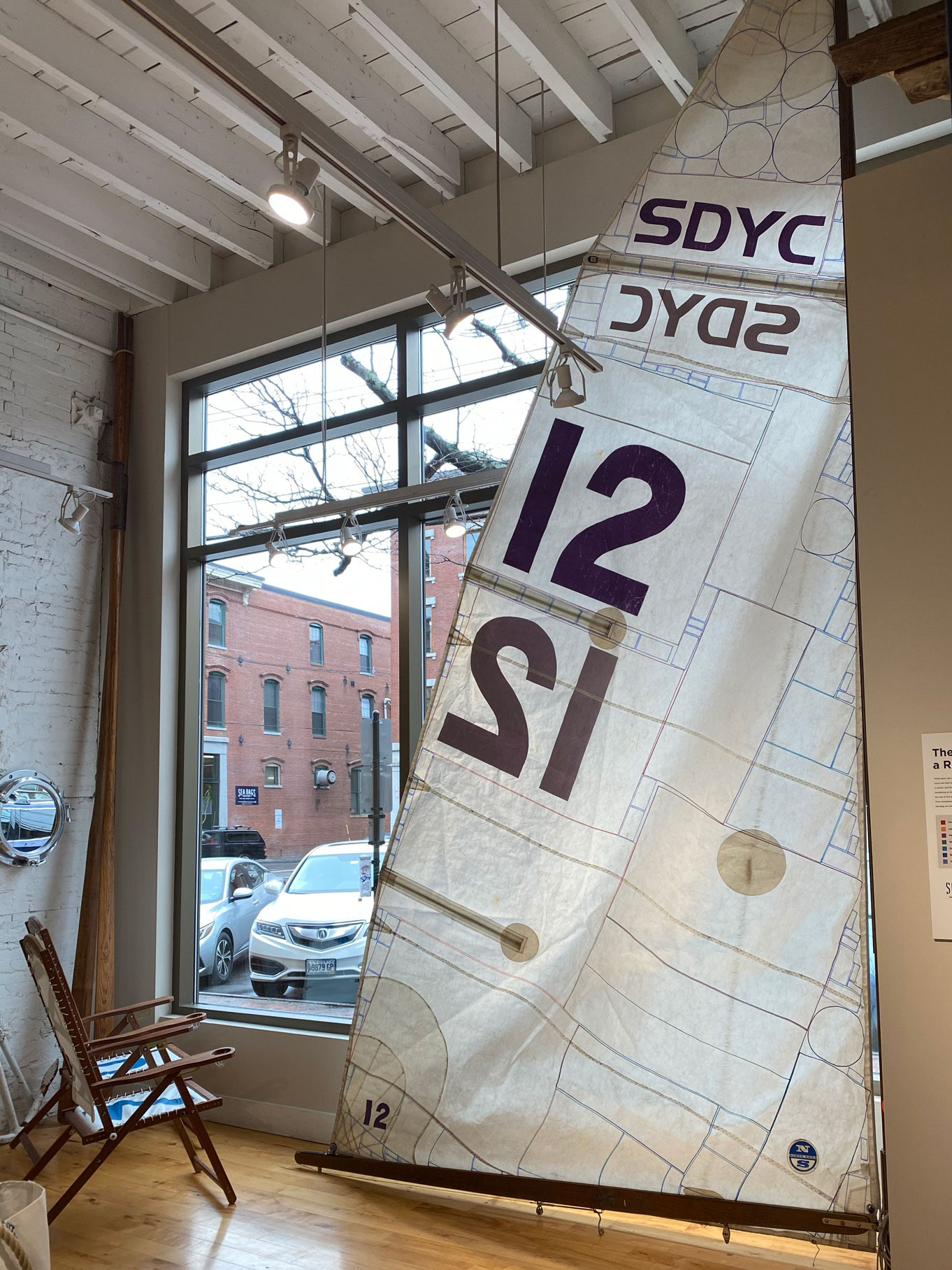 A sail is hanging on a mast in the store, with lines showing how all parts of a sail are salvaged
