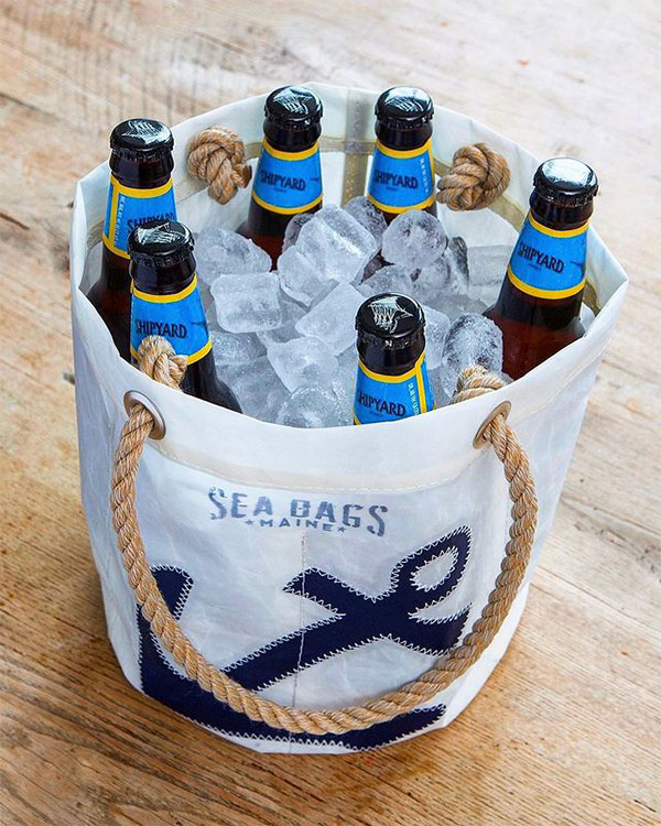 a white recycled sail cloth beverage bucket with hemp rope handles, the Sea bags logo, and a navy anchor, sits on a table. The bucket is filled with six glass bottles and ice.