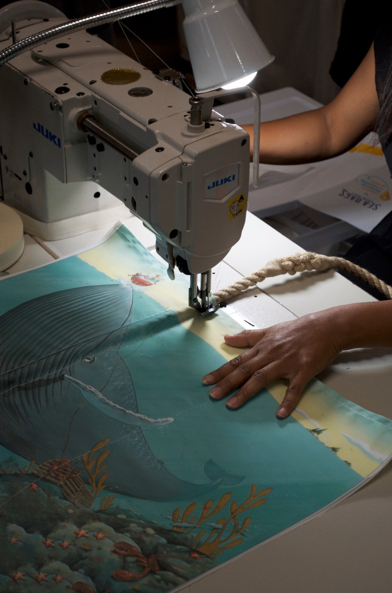 Chris Van Dusen's illustrations are transformed onto a recycled sail cloth tote at Sea Bags' headquarters