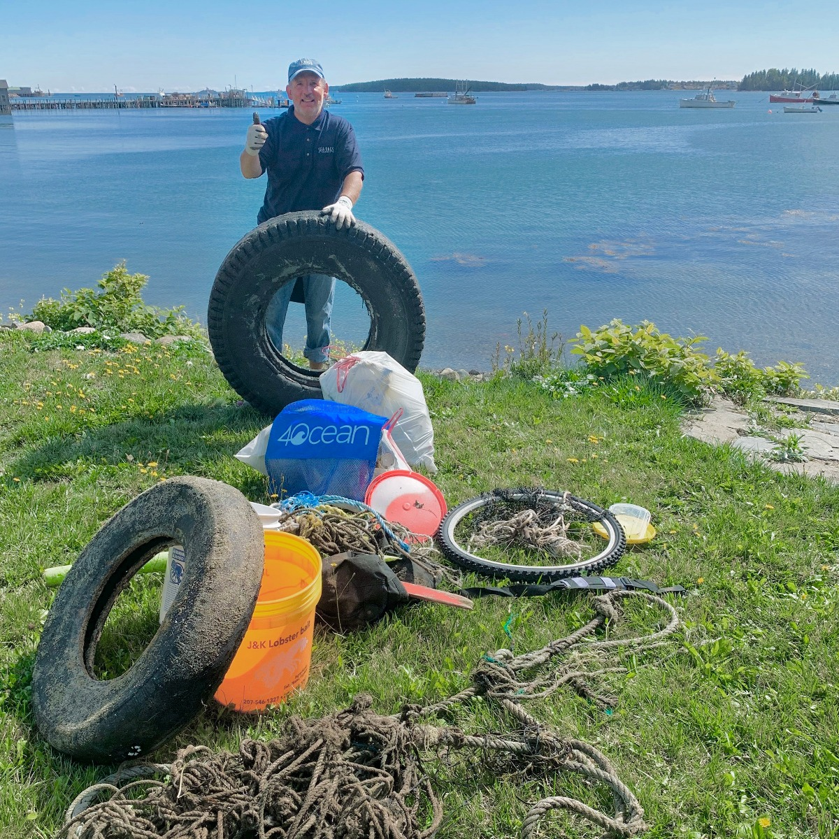 sea bags employee with trash collected on waterfront