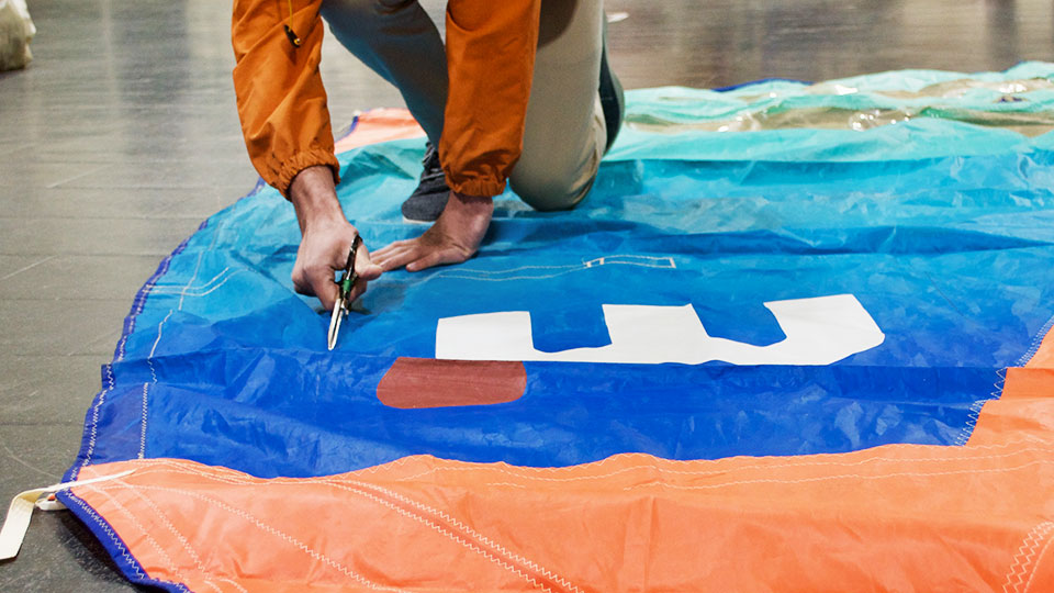 Cutting new recyled sails into pieces for tote bags