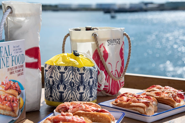 with the ocean in the background, a restaurant table is covered with recycled sail cloth bags featuring lobster prints and two trays of lobster rolls in the foreground