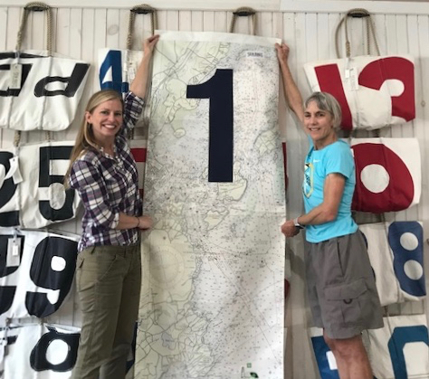 Sea Bags' staff show off the recycled sail cloth mile marker to Joan Benoit Samuelson