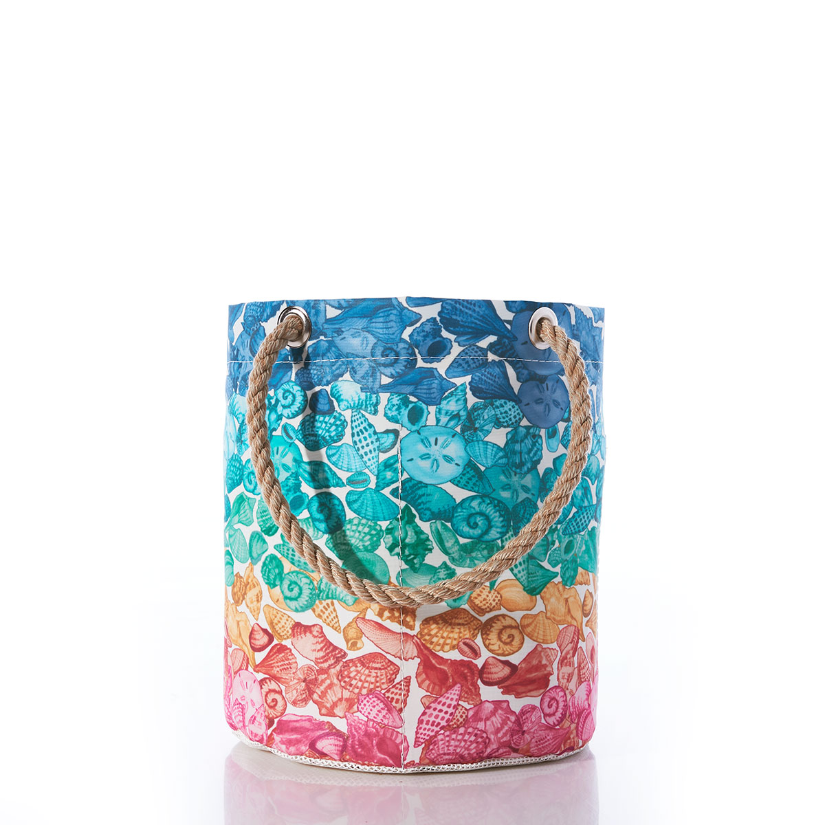 a recycled sail cloth beachcomber bucket with hemp handles features rows of a variety of seashells in rainbow colors, from top down blues, teals, sea greens, oranges and pinks