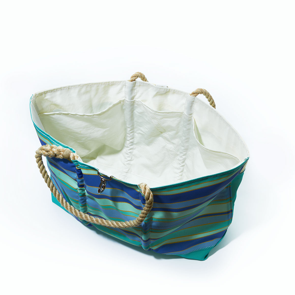 interior view, stripes of shades of blues are printed on this recycled sail cloth tote, with a seafoam green bottom and hemp rope handles