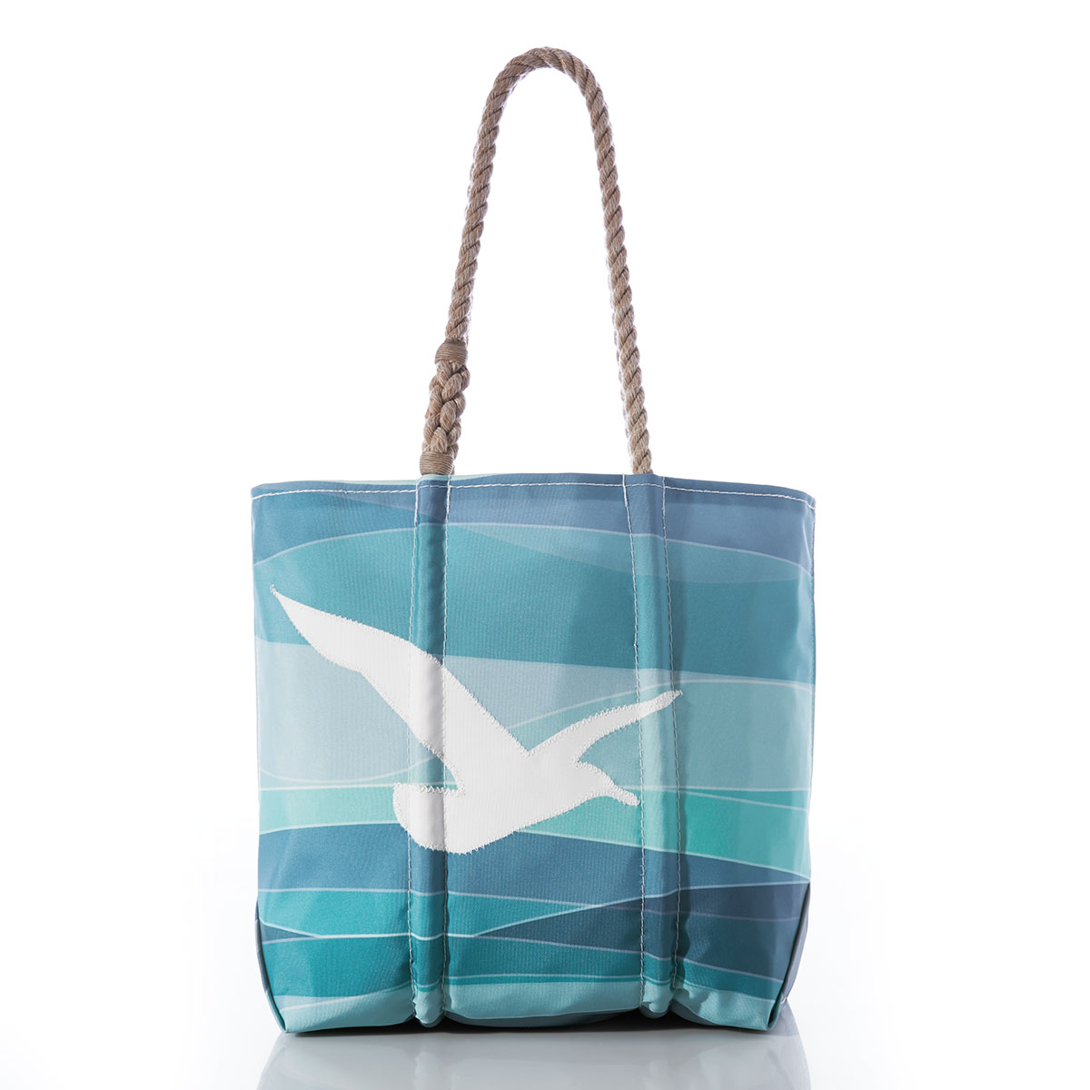 front of sail cloth tote bag, asymmetrical stripes in shades of blue and teal with a solid white outline of a seagull in the middle, and a hemp rope handle