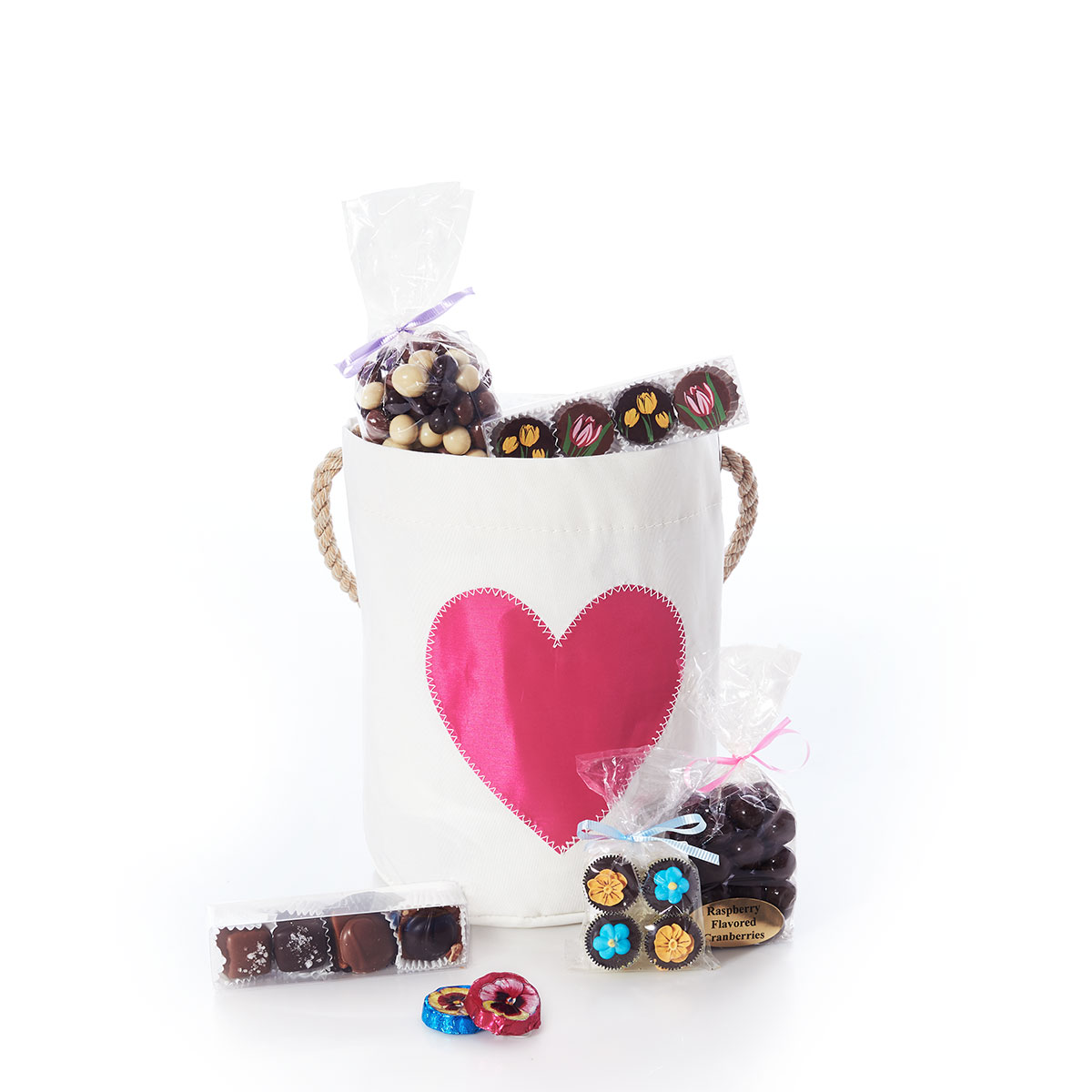 a white recycled sail cloth bucket with a white rope handle is embellished with a fuchsia pink heart, and it is surrounded by the chocolate gift set