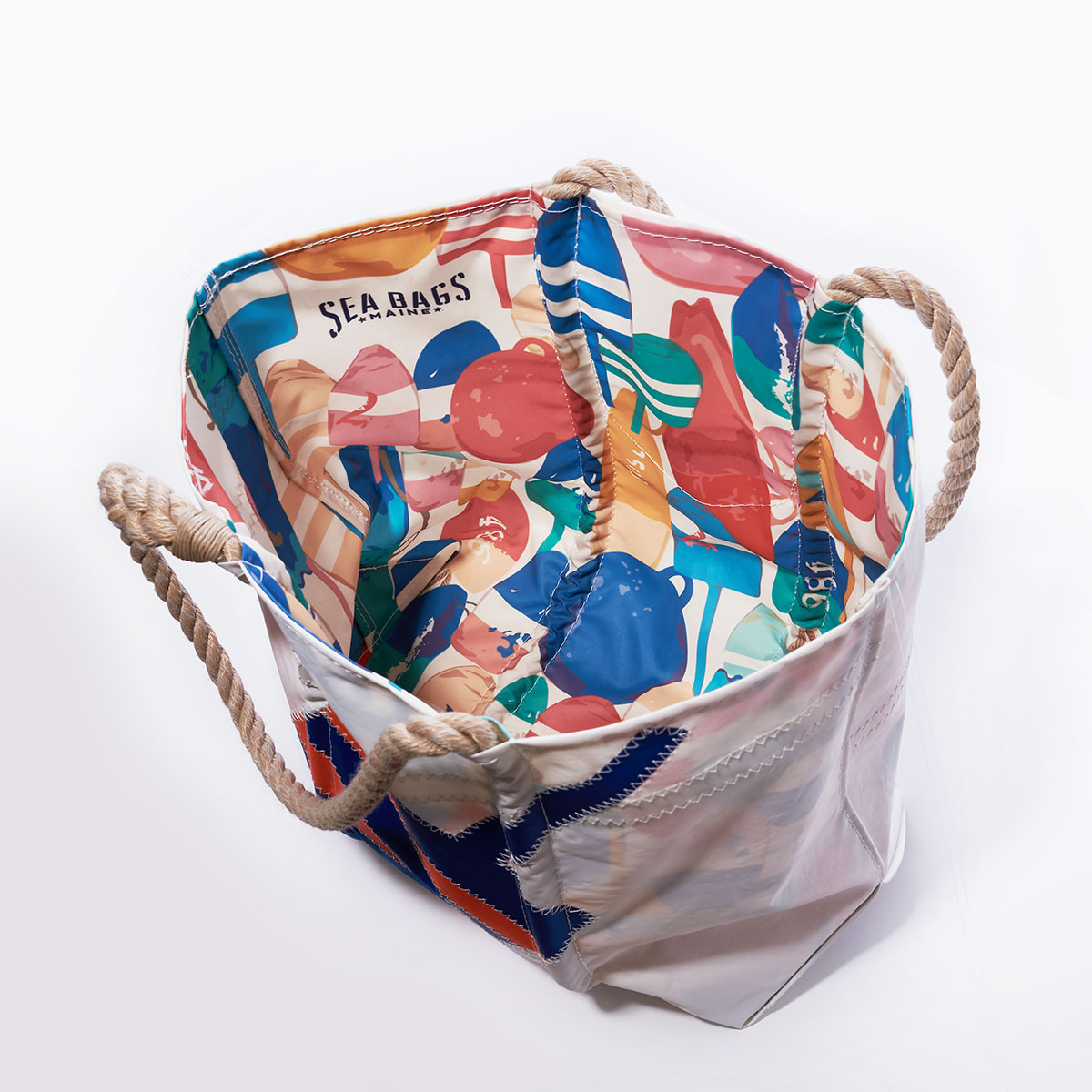 inside view showing the liner covered in an assortment of colorful buoys line the outside of a recycled sail cloth tote with hemp rope handles